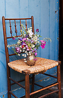 A vase of fresh flowers has been placed on an old chair outside the back door