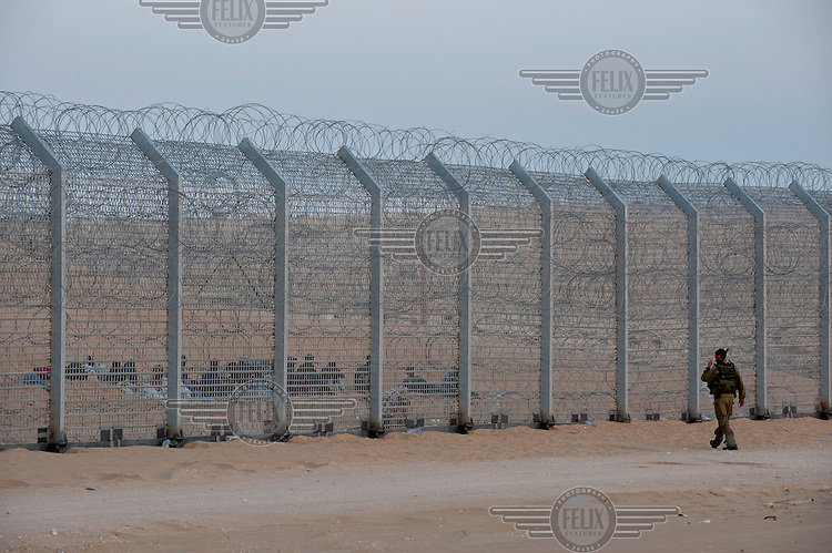 An Israeli soldier approaches a group of Eritrean migrants sitting on the ground behind a newly-built fence on Israeli/Egyptian border. They arrived a week earlier, crossed the old fence but got trapped by the new one. Israeli soldiers have been providing the group with water, but not allowing them into Israel. After eight days the Israeli government partially relented and allowed entrance for two women and one youth, while the rest of men returned to Egypt.