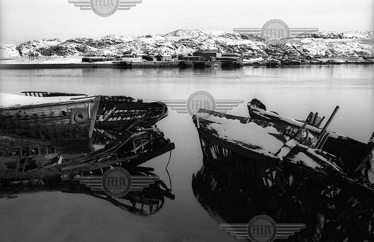Disused wrecks of old boats lie covered in snow in the water near the sea port of Murmansk on the Barent Sea.