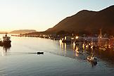 USA, Alaska, Sitka, fishing boats docked in Sitka Harbor at sundown, one boat returns from fishing before dark settles in