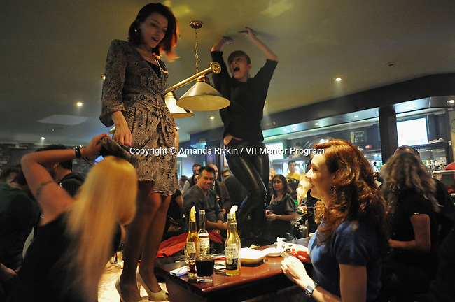 Women dance on the tables at Shakespeare bar, an expat bar popular with oil workers, in Baku, Azerbaijan on March 18, 2012.