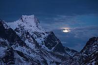 Winter moon next to Storskiva mountain peak, Moskenesøy, Lofoten Islands, Norway
