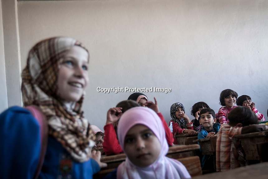 In this Thursday, Sep. 26, 2013 photo, Syrian children attend the public school in Madaya village as classes started in the Idlib province countryside of Syria. Children have come back to school in the rebel controlled territory despite the constant threaten of shelling and the ongoing fighting, and public schools still operating financially under the Syrian government administration. (AP Photo)