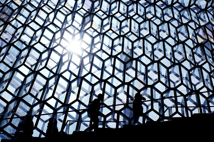 Silhouette of people climbing stairs in front of glass facade of Harpa Concert Hall, Reykjavik, Iceland