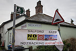 """© Joel Goodman - 07973 332324 . 26/01/2014 . Salford , UK . A banner reading """" Salford says no fracking anywhere """" suspended between signposts at the entrance to the approach road to the fracking site , on Barton Moss Road . Approximately 500 protesters march to an iGas fracking exploration site at Barton Moss , Salford , today (Sunday 26th January 2014) . They walk along the A57 road , blocking traffic as they do . A long term protest camp has been established on an access road leading to the site and today (26th January) protesters from other areas of the country travelled to the site to join with other protesters against fracking . Photo credit : Joel Goodman"""