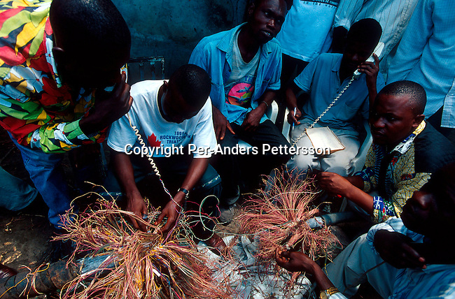dicocon00180 .Congo. Kinshasa. Technology, communication. Workers for the Congolese state Telephone Company examining hundreds of broken phone lines wires on February 28, 2002 on a busy street corner in central Kinshasa. They are trying to match the broken lines to fix them. The Congolese economy and infrastructure is in total disarray after 40 years of independence from Belgium. The country was fleeced by the former strongman Mobuto who together with his government stole most foreign aid money and the proceeds from the wealth of minerals in the country..©Per-Anders Pettersson/iAfrika Photos