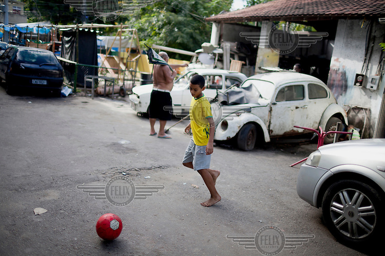 A boy plays football (soccer) in the Tavares Basto favela.