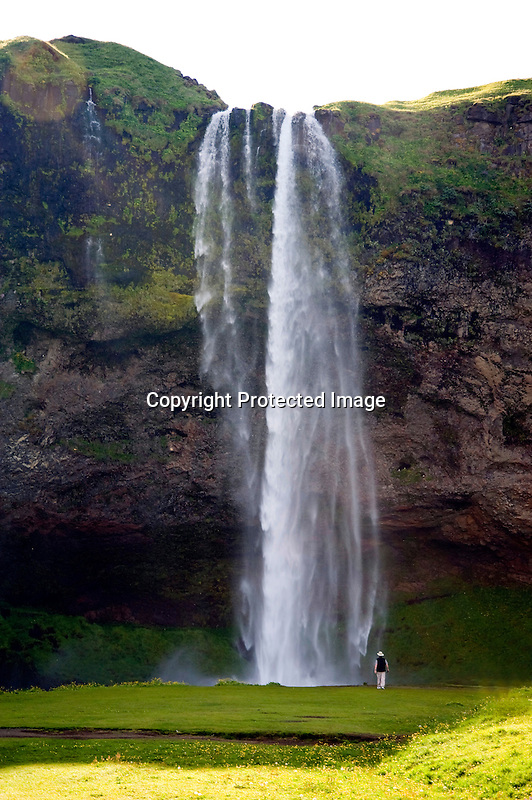 Person Enjoying Close-Up View of Seljalandsfoss Waterfall on the South Coast of Iceland