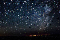 Meteor and the Milky Way photographed in New Mexico.  The red lights at the bottom is a distant wind farm.