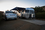 Airstream travel trailer and GMC Yukon SUV in camp spot
