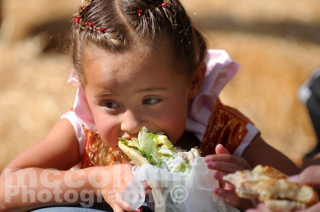 Tova Ekholm, 3, of Cupertino, chows down  at the Northern California Renaissance Faire held at Casa De Fruta Sunday afternoon...