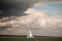 Sailing boat urgently heading for port to avoid the gathering cumulus storm clouds at sea.