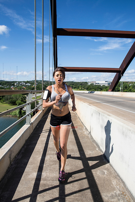 Sporty African-American female running on the 360 Bridge on Lake Austin, Texas.