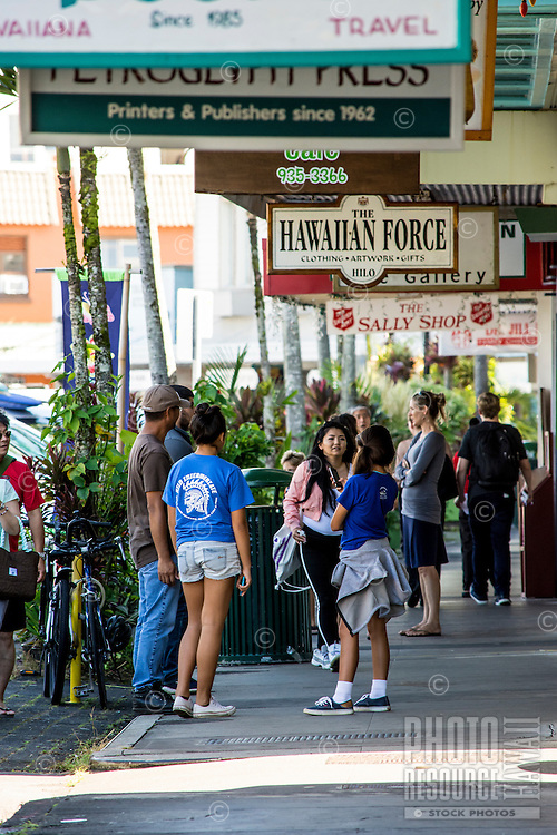 Visitors and residents converse along the waterfront by Kamehameha Avenue in downtown Hilo, Big Island of Hawai'i.