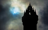 Picture shows today's solar eclipse as seen above the Wallace Monument in Central Scotland at 9.33am - the UK and northern Europe have glimpsed the best solar eclipse since 1999 when the area was plunged into darkness as the Moon came between the Earth and the Sun. The deep shadow formed first in the North Atlantic and then swept up into the Arctic, ending at the North Pole. In all parts of the UK the eclipse reached at least 83% and the darkness peaked at about 09:35 GMT. Clear viewing opportunities were restricted by the cloud cover that shrouded much of the country, which will not see a solar eclipse on this scale again until 2026. The National Wallace Monument - known as the Wallace Monument - stands on the summit of Abbey Craig, a hilltop at near Stirling in Scotland. It commemorates Sir William Wallace, a 13th-century Scottish hero. Completed in 1869 to the designs of architect John Thomas Rochead, the monument is a 67-metre (220 ft) sandstone tower, built in the Victorian Gothic style on a spot where from where Wallace was said to have watched the gathering of the army of King Edward I of England, just before the Battle of Stirling Bridge - picture by Donald MacLeod 20.3.15 clanmacleod@btinternet.com www.donald-macleod.com all rights reserved 07702319738