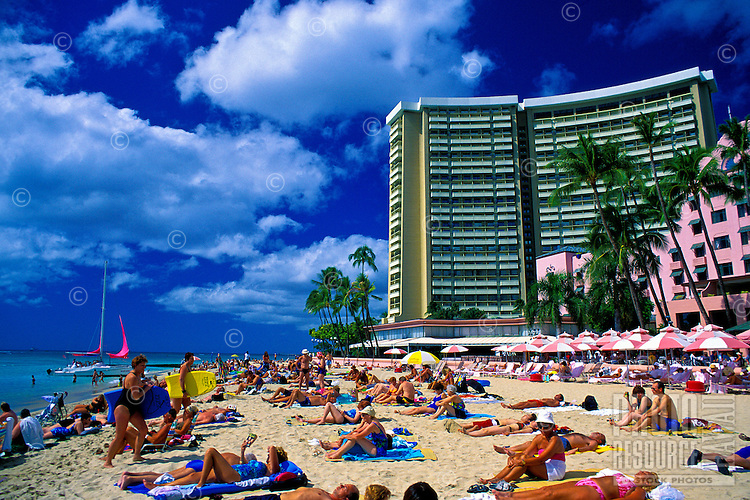 Tourists sunbathe at world famous Waikiki beach, with the Sheraton Waikiki and Royal Hawaiian Hotel in the background.