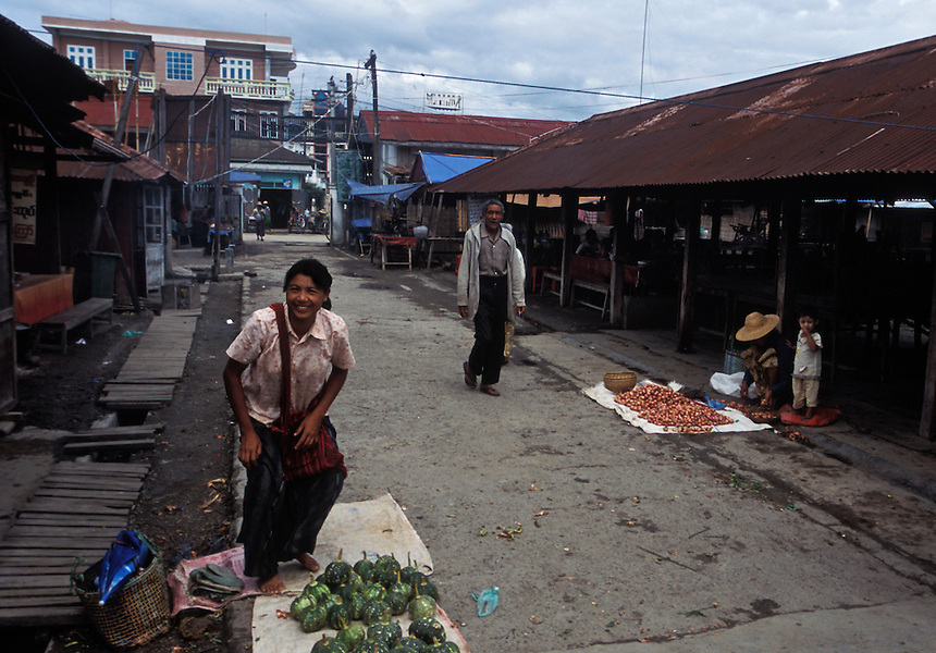 A woman stands to greet the photographer at the delapidated Nyaungshwe town market, Shan State, Burma, 2006.