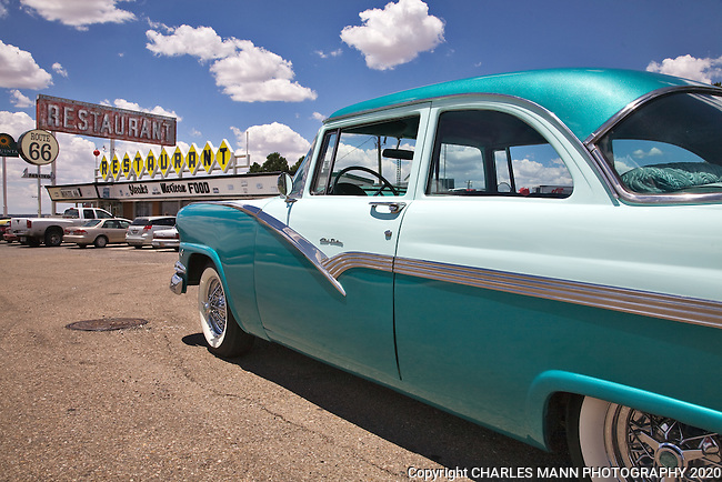 A two toned 1956 Ford Club Sedan gleams  in the sun in front of a period diner on old Route 66 in Santa Rosa, New Mexico.