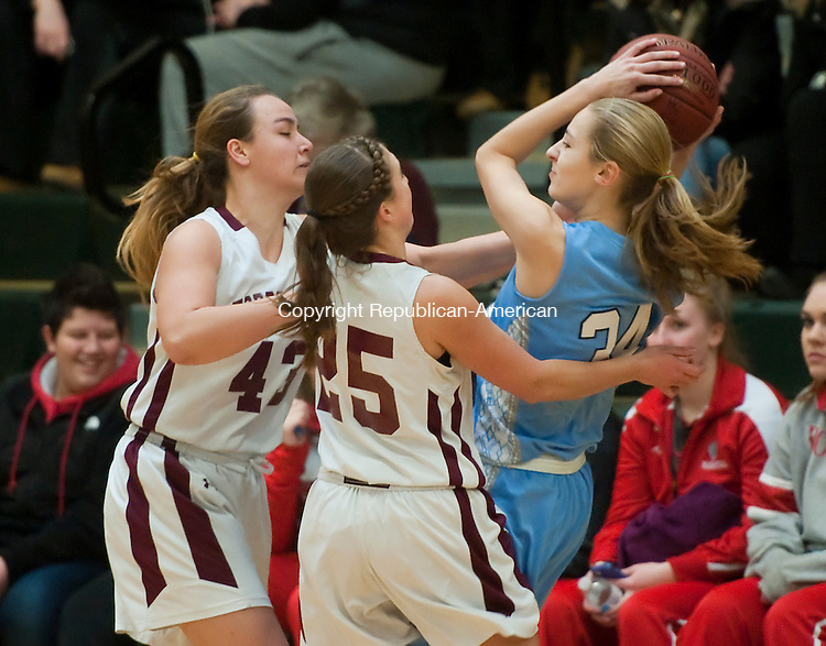 WATERBURY,  CT-022115JS05-  Oxford's Melanie Cianciola (34) tries to fight her way out of a trap by Torrington's Caitlyn Cornish (43) and Shelby Howe (25) during their NVL basketball tournament game Saturday at Holy Cross High School in Waterbury.<br /> Jim Shannon Republican-American