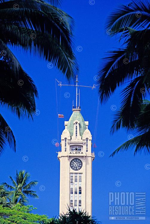 Aloha Tower framed by palms with blue sky.