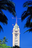 Aloha Tower framed by palms with blue sky.