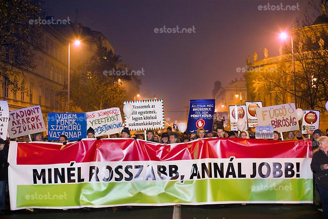 """UNGARN, 21.12.2018, Budapest V. Bezirk. Satirischer Marsch der """"Zweischwaenzigen Hundepartei"""" MKKP gegen das von der Fidesz-Regierung eingebrachte """"Sklavengesetz"""", das die Zahl der moeglichen Ueberstunden massiv erhoeht und ihre Abrechnung erschwert. –Motto des Marsches ist dieses Mal """"Je schlimmer, desto besser!"""" Tafeln: """"Ich moechte ein Stadion gebaehren!"""", """"Froher Boss, trauriger Sonntag"""", """"Bruederliche Traenengas-Pipeline aus der Sowjetunion"""", """"Schluss mit den Elite-Unversitaeten, alle auf die Berufsschule!"""", """"Stoppt Bruessel, sie schicken zu viel Geld"""", """"Abhaengige Justiz"""".   Satirical march by the """"Dog-With-Two-Tails party"""" MKKP against the """"slave law"""" proposed by the Fidesz government, allowing for a massive rise in overtime work while hampering its payoff. The march's slogen is this time: """"The worse the better!"""".  © Martin Fejer/estost.net"""