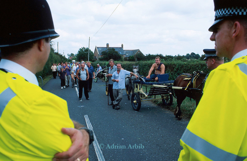 Romanies queue up at a  road  block in  Horsmandean Kent, having  been prevented access to the green in the centre  of the town.   After 300 years the  horsefair was stopped by hundreds of police in riot gear.  <br /> Only one horse and trailer got permission to parade around the green in the centre of the town whereupon local residents applauded the Romanies.