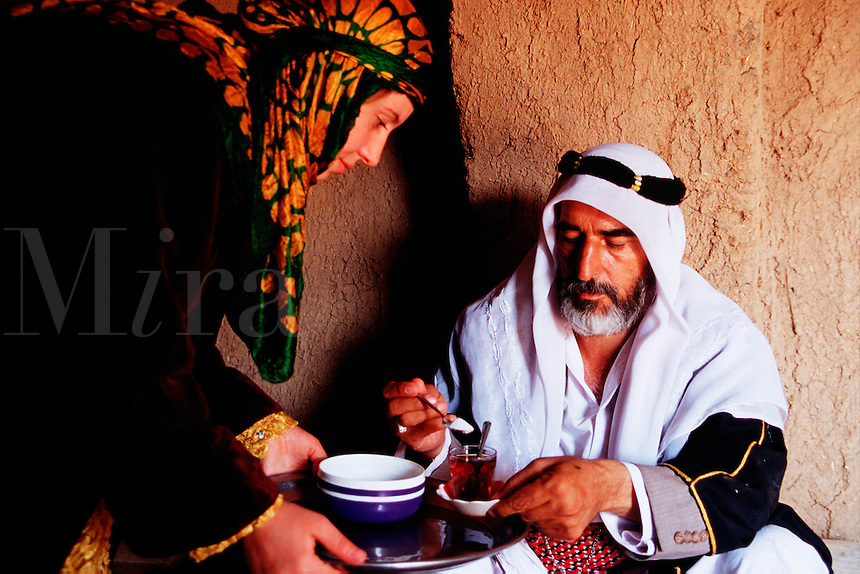 A Kurdish woman serves tea to an Arab man. Harran, Turkey.