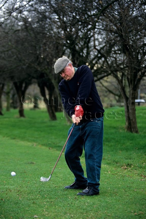 Senior golfer tees off on a golf course