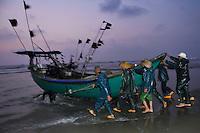 Fishermen launching their boats at dawn on Nan San island, Guangdong province, China