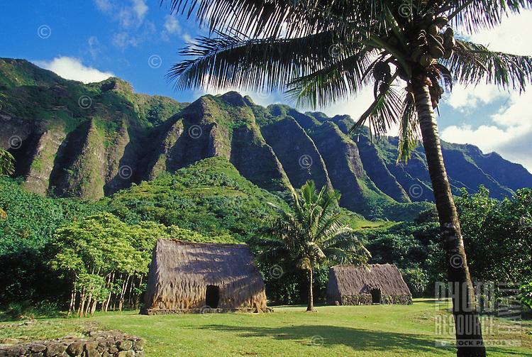 Traditional Hawaiian huts with crenelated mountain range at Kualoa Ranch, windward Oahu