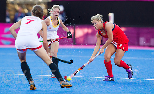02 AUG 2012 - LONDON, GBR - Georgie Twigg (GBR) (right) of Great Britain attempts to evade a challenge from Judith Vandermeiren (BEL) (left) of Belgium during the London 2012 Olympic Games preliminary round hockey match between the two countries at the Riverbank Arena in the Olympic Park at Stratford, Great Britain .(PHOTO (C) 2012 NIGEL FARROW)