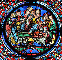 Mary lies in her deathbed surrounded by the 12 apostles, who have been miraculously transported from their missions to her bedside. John leans over the Virgin and Paul is at the foot of the bed, all with expressions of sadness. The Death of the Virgin, from the Glorification of the Virgin stained glass window, in the nave of Chartres Cathedral, Eure-et-Loir, France. This window depicts the end of the Virgin's life on earth, her dormition and assumption, as told in the apocryphal text the Golden Legend of 1260. Chartres cathedral was built 1194-1250 and is a fine example of Gothic architecture. Most of its windows date from 1205-40 although a few earlier 12th century examples are also intact. It was declared a UNESCO World Heritage Site in 1979. Picture by Manuel Cohen