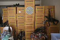 Photographer: Rick Findler..06.10.12 A dart-board hangs up amongst weapons and belongings where FSA members sleep inside the city of Aleppo.