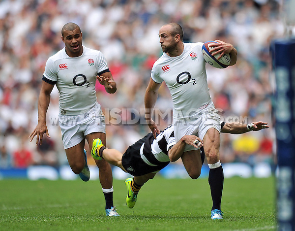 Charlie Sharples is tackled in possession. International match between England and the Barbarians on June 1, 2014 at Twickenham Stadium in London, England. Photo by: Patrick Khachfe / Onside Images