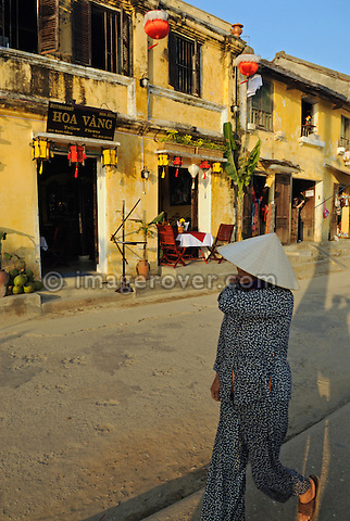 Asia, Vietnam, Hoi An. Hoi An old quarter. Vietnamese woman passing the cafe restaurant Hoa Vang on the Bach Dang river promenade. The historic buildings, attractive tube houses, and decorated community halls have 1999 earned Hoi An's old quarter the status of a UNESCO World Heritage Site. To protect the old quarter's character stringent conversation laws prohibit alterations to buildings, as well as the presence of cars on the roads.