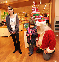STAFF PHOTO ANDY SHUPE - Jim Stines of Springdale, right, pauses to speak with Maci Neil, 4, as Ashley Donohew, both of Springdale, laughs Wednesday, Dec. 24, 2014, while shopping in the Northwest Arkansas Mall. Stines was shopping on Christmas Eve as he normally does and stopped to talk to children and have his photograph made.