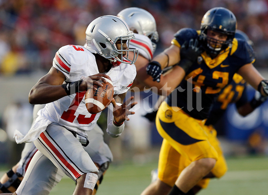 Ohio State Buckeyes quarterback Kenny Guiton (13) scrambles out of the pocket past California Golden Bears defensive lineman Dan Camporeale (43) during the fourth quarter of the NCAA football game at Memorial Stadium in Berkeley, California on Sept. 14, 2013. (Adam Cairns / The Columbus Dispatch)