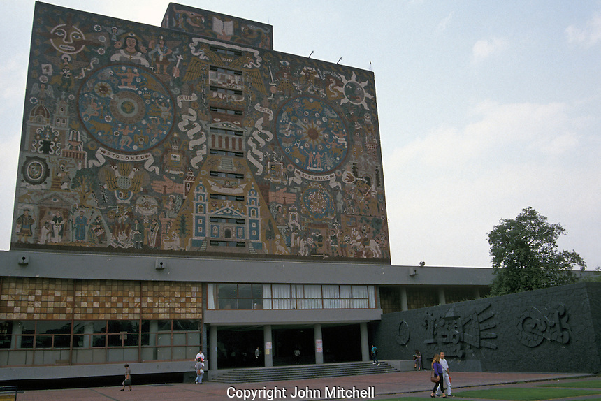 University students with the Central library in the background, Universidad Nacional Autonoma de Mexico or UNAM in Mexico City. The library is covered in murals by Juan O'Gorman. This university campus is a UNESCO World Heritage site.