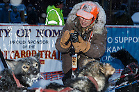 Iditarod fan Carolyn Drake takes a photo of a Charlie Bejna dog at the Nome finish chute Friday March 14 during the 2014 Iditarod Sled Dog Race.<br />