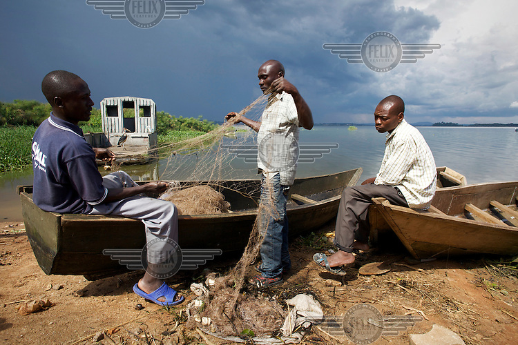 Fishermen repair their nets on their pirogues at Ggaba landing site on the shore of Lake Victoria in Kampala.