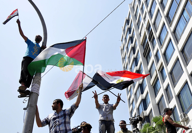 Demonstrators wave Egyptian (top) and Palestinian flags during a protest outside the Israeli embassy in Cairo on August 20, 2011. Egypt decided to recall its ambassador from Israel to protest the deaths of policemen killed on the border, in the first diplomatic spat between the two nations since the fall of the Mubarak regime. Photo by Ahmed Asad