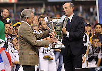 CARSON, CA - DECEMBER 01, 2012:  Philip Anschutz of the Los Angeles Galaxy accepts the winners trophy from Don Garber during the 2012 MLS Cup at the Home Depot Center, in Carson, California on December 01, 2012. The Galaxy won 3-1.