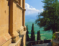 Tuscany, Italy, <br /> Sun warms the cathedral wall in Pienza's Piazzo Pio II and a stone pathway leads to views of the rolling hills and farms of the Val d'Orcia