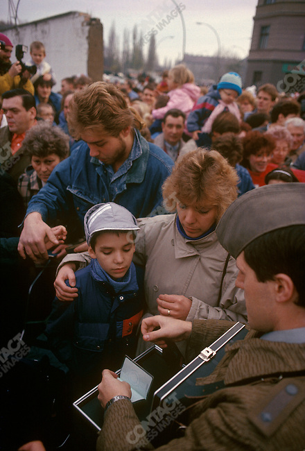 Opening of the Berlin Wall. East Berliners on their way to visit West Berlin have their passports stamped at a makeshift passport control center hastily set up by the East German authorities. Germany, November 1989