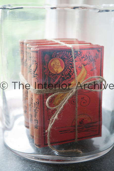 Vintage volumes of Swedish historical novels are displayed in a glass vase in the kitchen