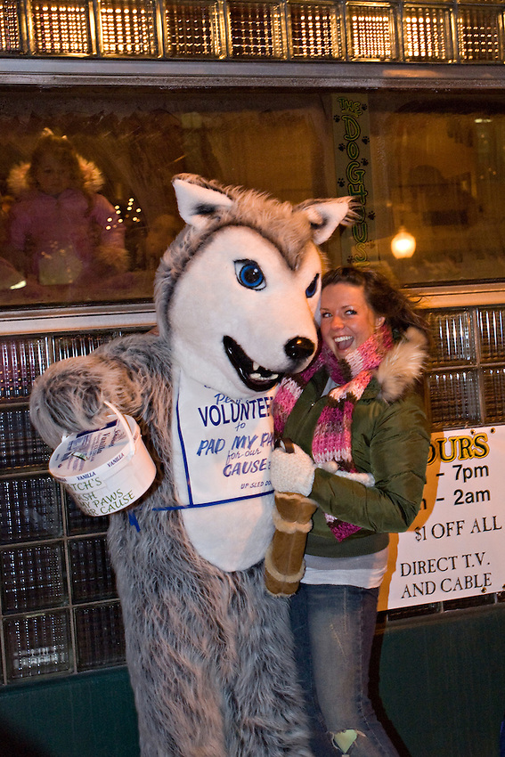 A spectator poses for a photo with a sled dog mascot during the UP 200 Sled Dog Championship race.