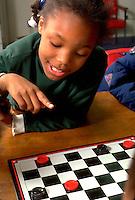 Girl age 6 contemplating next checker move.  St Paul  Minnesota USA