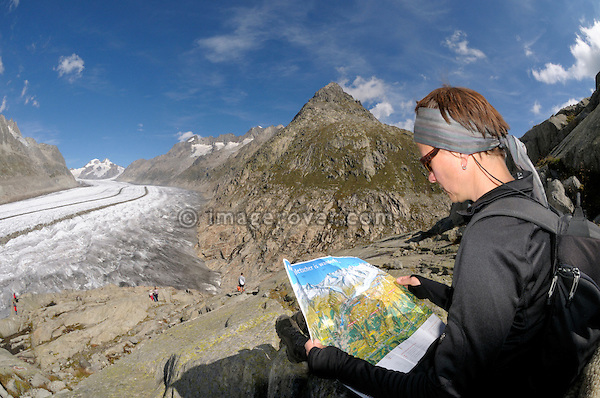 Switzerland, Valais, Western Europe, Jungfrau Region, Aletsch Glacier (UNESCO world heritage site). Tourist with map on the panorama trail nr. Märjelensee.  --- Model release available.