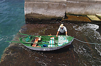 Fisherman bringing small fishing boat ashore. Tenerife, Canary Islands.